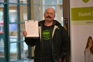 Camosun student Blair Roche holding his petition (photo by Jill Westby/Nexus).